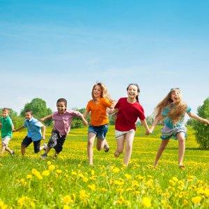 group of children running through the field