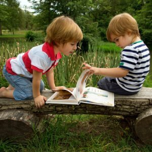 twin brothers enjoying reading a book together